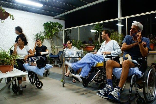 5 osob se zdravotním posezení sedí v místnosti a pracují
