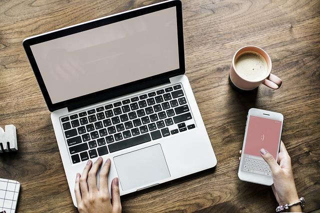 Ruka položená na klávesnici u notebooku, vedle položený mobil a káva