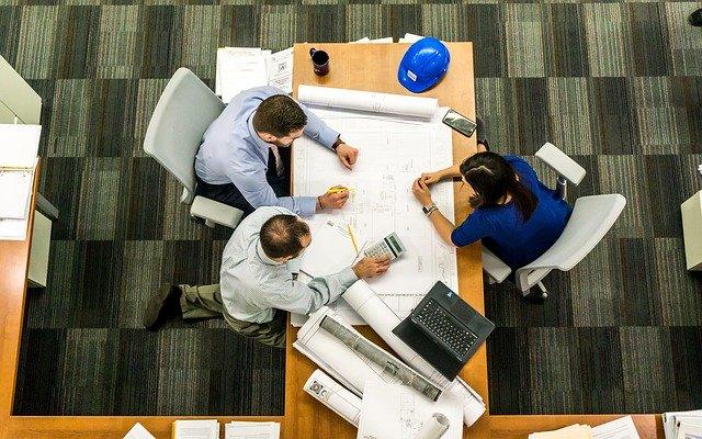 Společná schůzka u stolu, kde se domlouvají lidé na tom, jak budou spolupracovat.