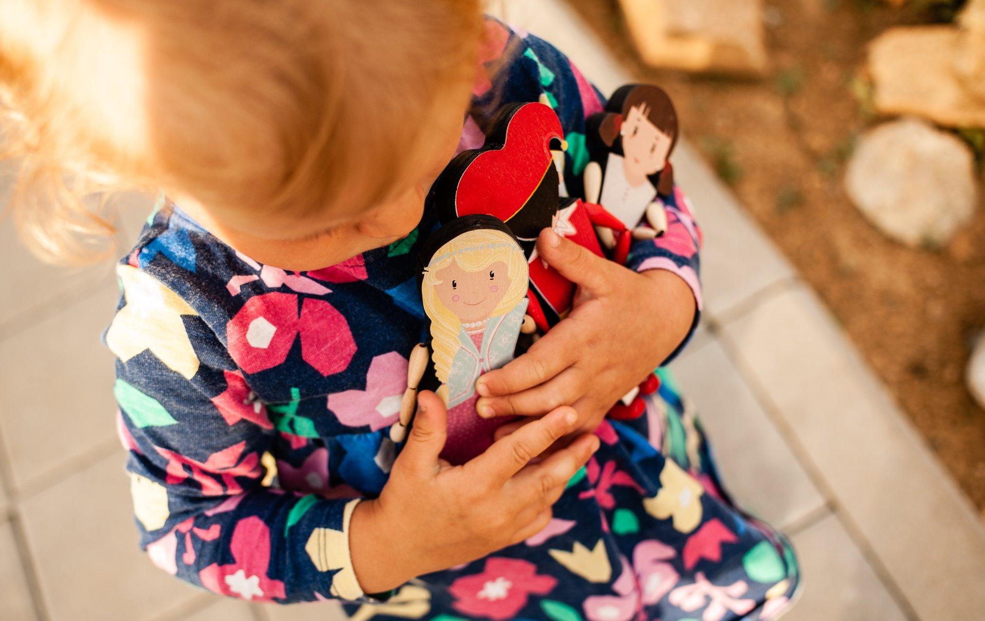 holčička, která má v ruce dřevěnou hračku.