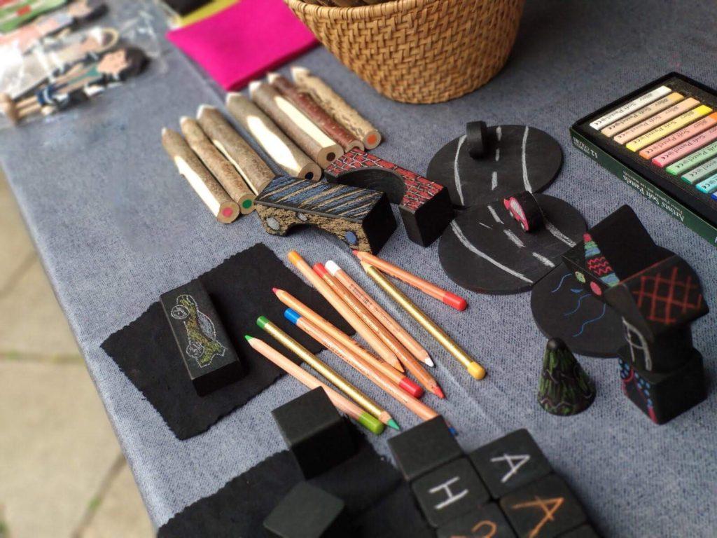 Fotka stolu, na kterém leží pastelky, kostky a hračky, které si mohou děti pokreslit.